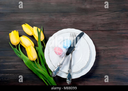 Place Setting for Easter, olored easter eggs and  bouquet of yellow tulips on a wooden background - Stock Photo