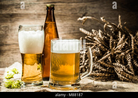Beer mugs, glasses, bottle on cloth with hop ,wheat - Stock Photo