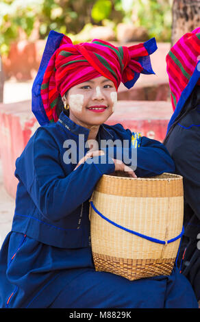 young Pa O lady wearing colourful headscarf with basket at Shwe Indein Pagoda complex, Inle Lake, Shan State, Myanmar - Stock Photo