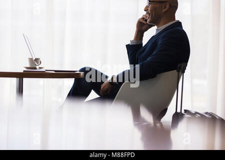 Businessman sitting at airport lounge and talking on cell phone. Male business traveler sitting at airport waiting - Stock Photo