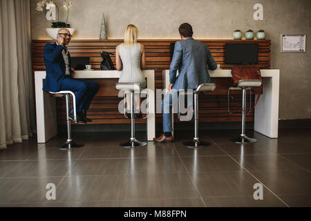 Rear view shot of travelers sitting at free internet service counter in airport. People at cyber corner in airport - Stock Photo