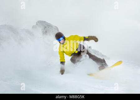 Fast young snowboarder snowboarding at backcountry slope. Ski resort concept. - Stock Photo