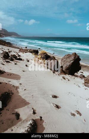 Huge volcanic stone boulder on spectacular white sand dunes of remote deserted beach Praia Grande. Ocean hitting - Stock Photo