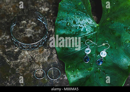 Wedding jewelry set of bride: earrings, two rings and silver bracelet on wooden background - Stock Photo