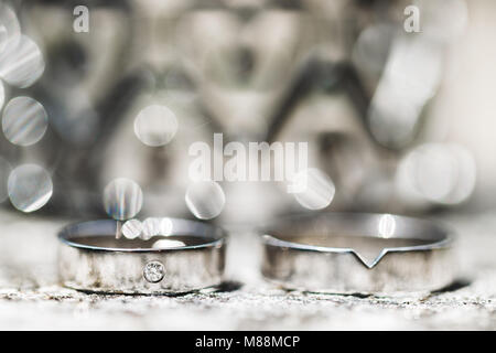 Wedding rings with precious stone close-up with beautiful blurred background and highlights - Stock Photo
