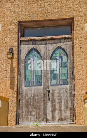 Front doors to a church made of bricks with two stained glass windows in shades of green and blue - Stock Photo