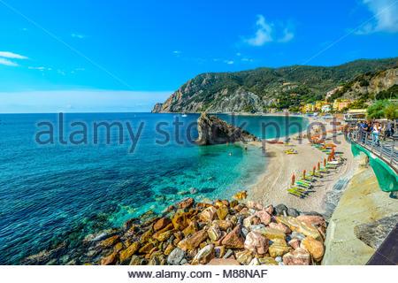 The sea and sandy beach Spiaggia di Fegina at the Cinque Terre Italy resort village of Monterosso al Mare with tourists - Stock Photo