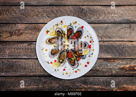 Plate of mussels in garlic sauce. - Stock Photo
