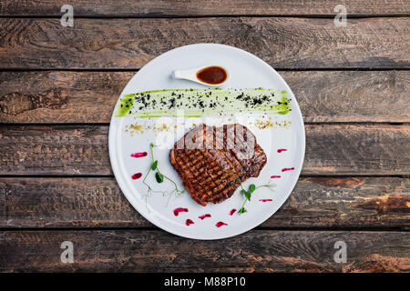 Grilled beef steak on a white plate. - Stock Photo