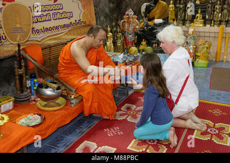 Ratchaburi ,Thailand- February 19,2018: Monk connects the protective thread of Sai Sin - Stock Photo