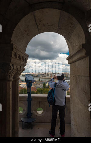 Tourist takes photo of Budapest Parliament as seen through arch in Matthias Church, Hungary. - Stock Photo