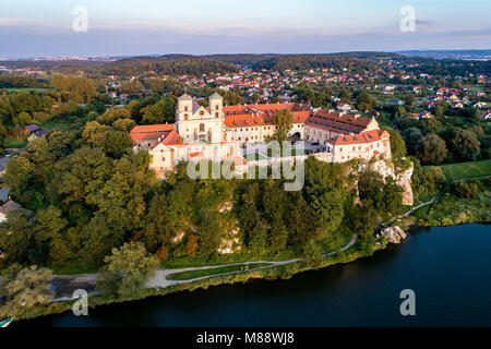 Benedictine monastery on the rocky cliff in Tyniec near Cracow, Poland, and Vistula River. Aerial view at sunset - Stock Photo