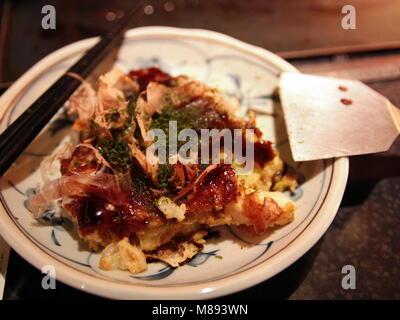 Japanese style Pizza - Okonomiyaki. Okonomiyaki is a Japanese savory pancake containing a variety of ingredients. - Stock Photo