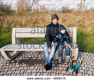 Man and young boy sitting on a wooden bench next to a child scooter at the Rataje park in Poznan, Poland - Stock Photo