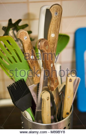 Mix of kitchen utensil including knives in a metal container in soft focus - Stock Photo