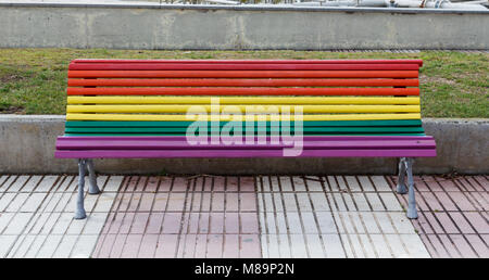 Bench painted in rainbow colors in the street - Stock Photo
