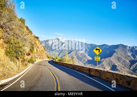 Sharp turn left sign in Yosemite National Park at sunset, California, USA. - Stock Photo