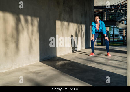 Female runner taking a break standing bent over and catching her breath after a running workout in city. - Stock Photo