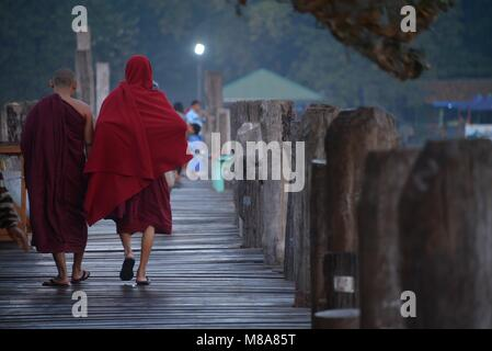 Two young monks walking in the wooden bridge - Stock Photo
