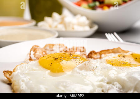 Traditional Israeli Breakfast with two fried eggs, yellow cheese, salad, a fresh roll and a cup of cappuccino. Closeup - Stock Photo