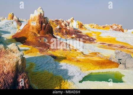 Yellow sulfuric volcanoes emitting toxic gas clouds, sulfur deposits white and green colors Danakil desert, the - Stock Photo