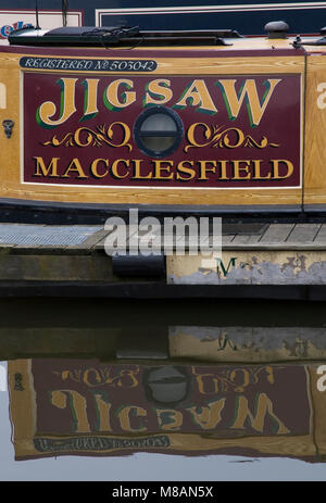 Close up of the side of the narrow boat Jigsaw moored at Macclesfield marina on the Macclesfield canal. - Stock Photo