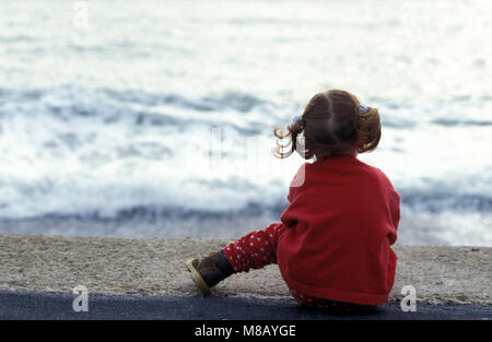 lone little girl sitting on beach watching waves come in - Stock Photo