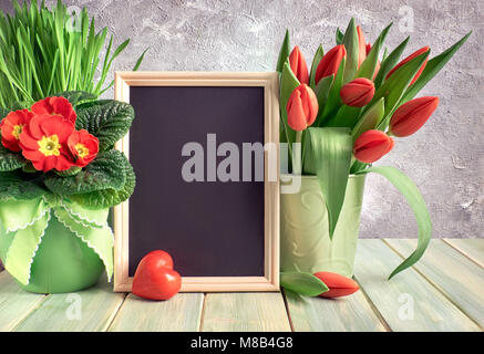 Easter composition with red stone heart and red Spring flowers on rustic wood. Text space on a blackboard with vertical - Stock Photo