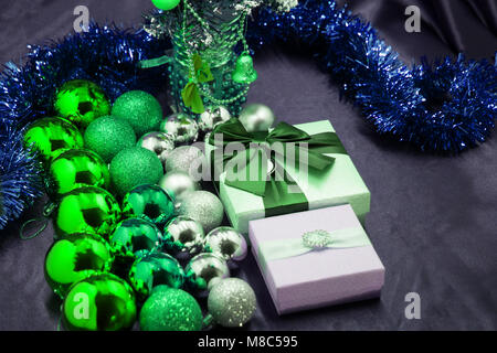 A gift with a red bow among decorative balls lies on a Christmas tree - Stock Photo