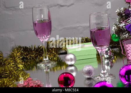 two glasses of cold champagne and Christmas decoration on the background of lights and brick wall. Purple - Stock Photo