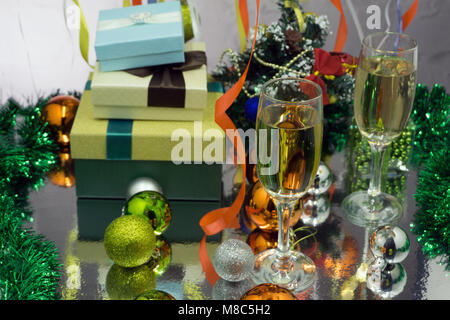 Abstract blurry background :Christmas or New Year. Champagne in glasses with candles, panettone and gift with red - Stock Photo