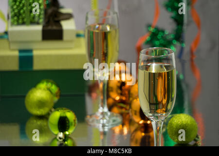 Two champagne glasses and christmas basket bottle, gifts with red satin ribbon, apples candy canes, pine cones branches, - Stock Photo