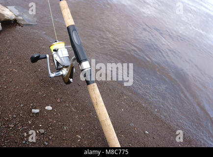 with spinning and reel on the summer lake - Stock Photo
