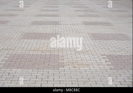 Texture of gray and yellow patterned paving tiles on the ground of street, perspective view. Cement brick squared - Stock Photo