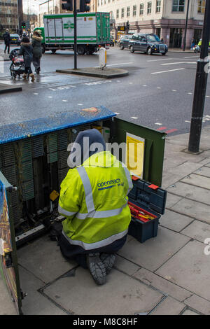 a BT or telecommunications engineer or technician working in a large exchange box or roadside cabinet connecting - Stock Photo