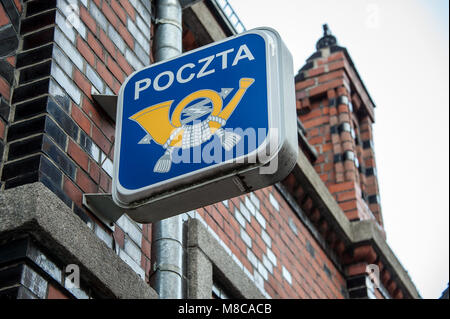 Post horn (postal service logo) on side of red brick building. Street sign, yellow image on blue background in historic - Stock Photo