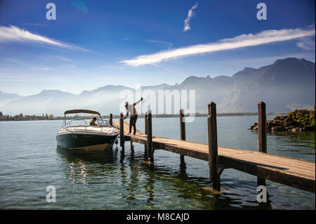 Peaceful lake scene with mountains behind. Woman and man secure motor boat at jetty on Lake Geneva (Lac Leman), - Stock Photo