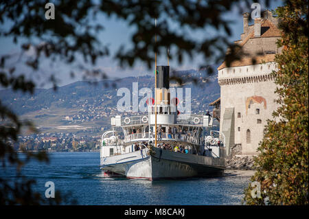 Historic paddle steamer at Chateau de Chillon on Lake Geneva, Beautiful scene, framed by leafy trees - Stock Photo