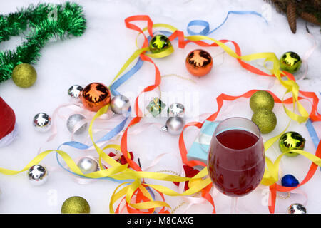 Two glasses of wine and gifts with a red satin ribbon, apples , pine cones, branches, gold ornaments garlands - Stock Photo