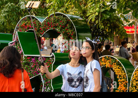 Two girls take a selfie using a selfie stick in front of Chinese Lunar New Year decorations, Ho Chi Minh City, Saigon, - Stock Photo