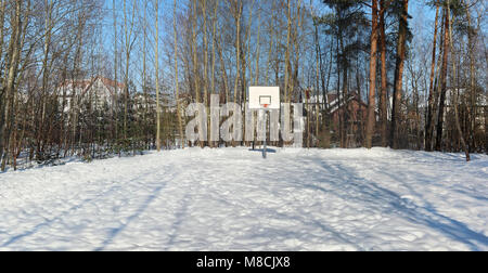 An empty basketball court in a snow-covered forest near a European village. Panoramic collage from several outdoor - Stock Photo