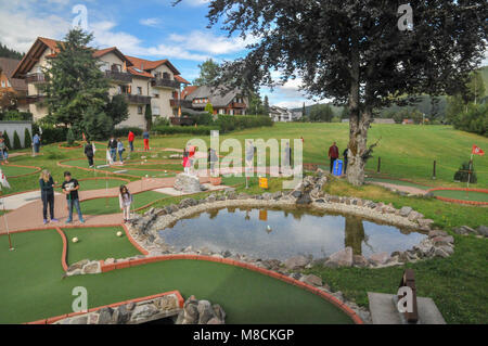 Families putting on a mini golf or putting course - Stock Photo