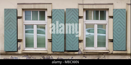 Two windows in the old house with open wooden shutters.. In the glass a white car is reflected. - Stock Photo