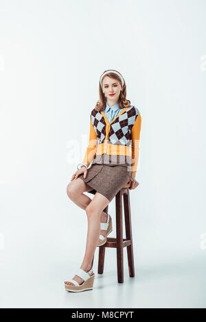 attractive retro styled girl sitting on wooden chair and looking at camera on white - Stock Photo
