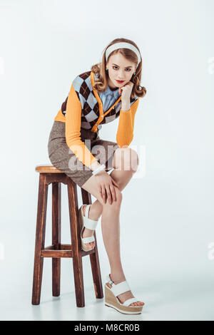beautiful retro styled girl sitting on wooden chair and looking at camera on white - Stock Photo