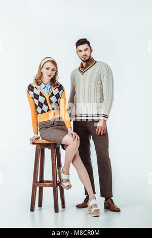 beautiful retro styled couple with wooden chair looking at camera on white - Stock Photo