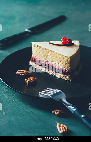 close up view of piece of cake on plate with hazelnuts and fork - Stock Photo