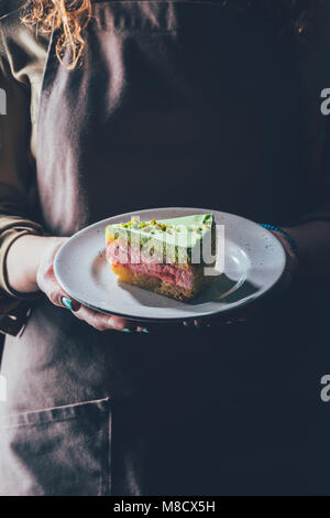 close up view of woman holding piece of homemade cake on plate in hands - Stock Photo