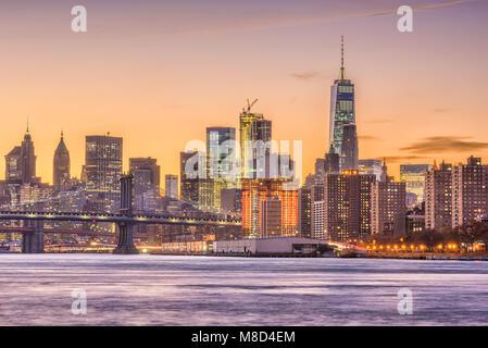 New York City, USA skyline on the East River with Brooklyn Bridge at dusk. - Stock Photo