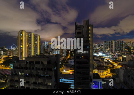 Singapore cityscape with rooftop view of apartment buildings with dramatic cloudy night sky - Stock Photo